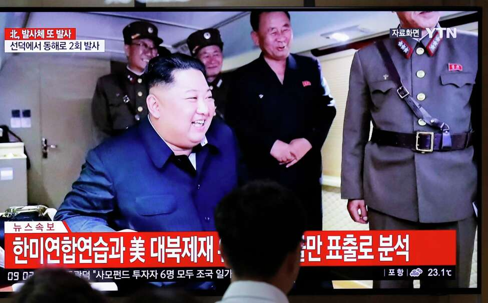 People watch a TV news program reporting North Korea's firing of projectiles with a file image of North Korean leader Kim Jong Un at the Seoul Railway Station in Seoul, South Korea, Saturday, Aug. 24, 2019. North Korea fired two suspected short-range ballistic missiles off its east coast on Saturday in the seventh consecutive week of weapons tests, South Koreaa€™s military said, a day after it threatened to remain Americaa€™s biggest threat in protest of U.S.-led sanctions on the country. The Korean letters read:
