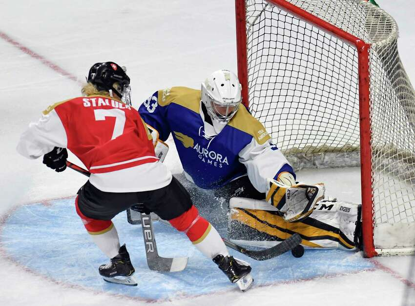 Team World's Lara Stalder (7) shot is blocked Team Americas' goaltender Kaitlin Burt (33) in the first period of a ice hockey game during the Aurora Games at the Times Union Center on Friday, Aug. 23, 2019 in Albany, N.Y.(Hans Pennink / Special to the Times Union)