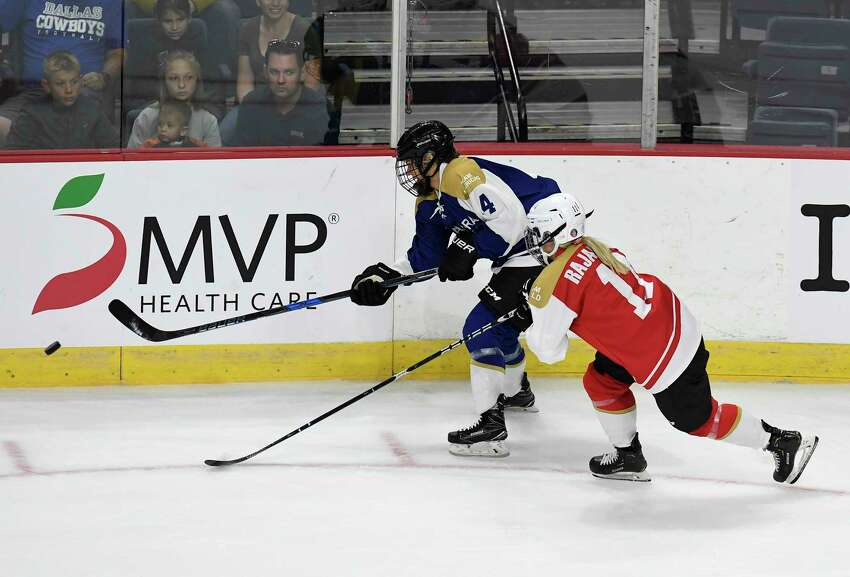 Team Americas' Emily Janiga (4) moves the puck past Team World's Annina Rajahuhta (11) in the first period of a ice hockey game during the Aurora Games at the Times Union Center on Friday, Aug. 23, 2019 in Albany, N.Y.(Hans Pennink / Special to the Times Union)