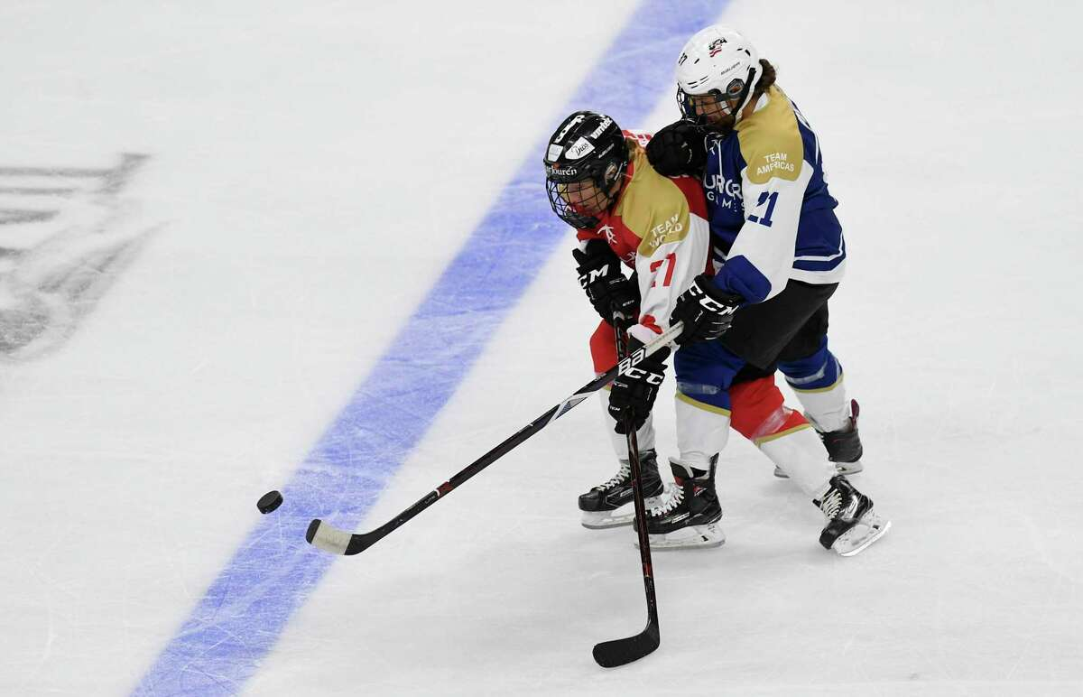 Team World's Rebecca Stenberg (27) and Team Americas' Amanda Pelkey (21) chase the puck in the first period of a ice hockey game during the Aurora Games at the Times Union Center on Friday, Aug. 23, 2019 in Albany, N.Y.(Hans Pennink / Special to the Times Union)