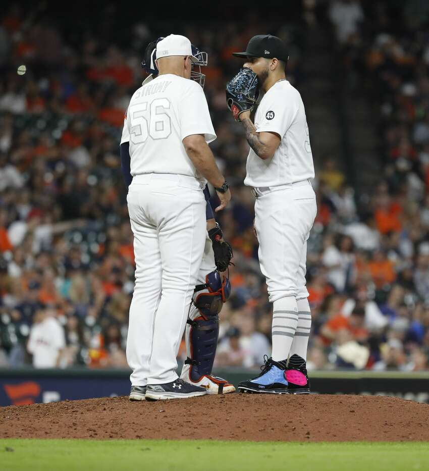 Houston Astros relief pitcher Roberto Osuna (54) talks with pitching coach Brent Strom (56) during the ninth inning of an MLB game at Minute Maid Park, Friday, August 23, 2019.
