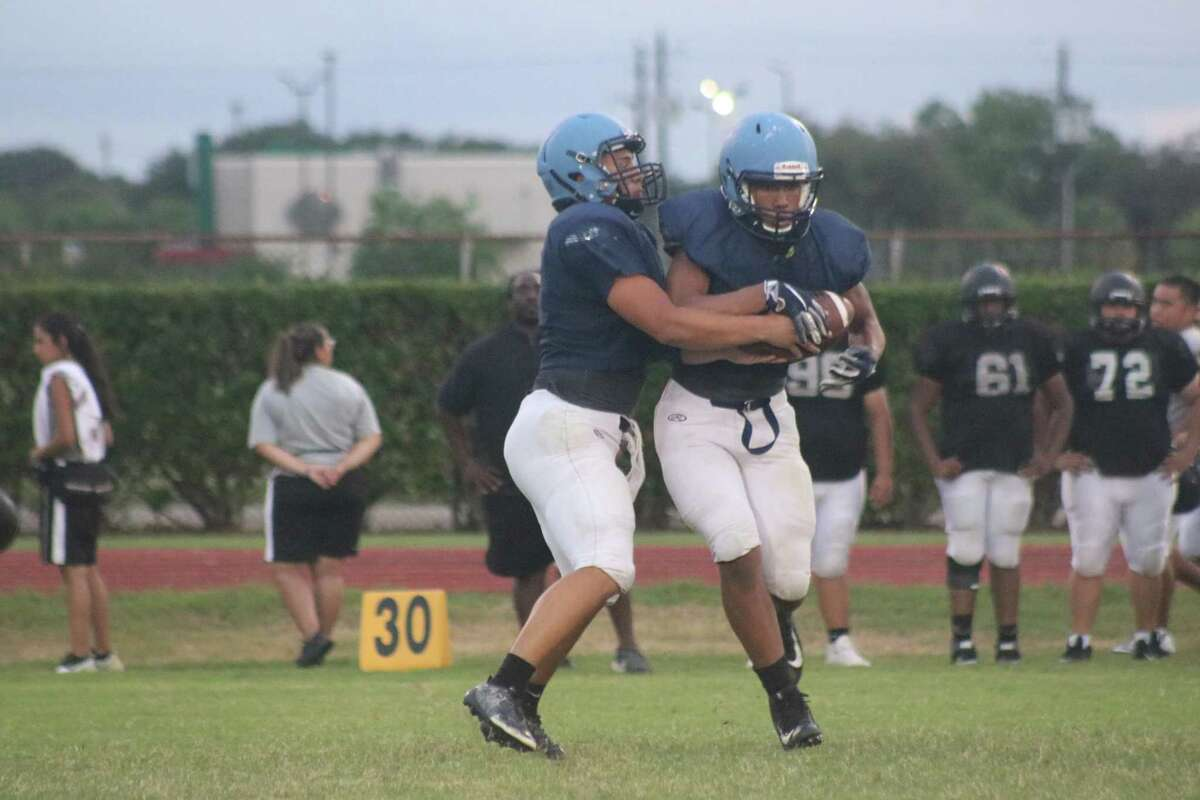 Not the smoothest of handoffs in the backfield, Sam Rayburn's quarterback and running back struggle to exchange the ball during Friday night's scrimmage with Galena Park.