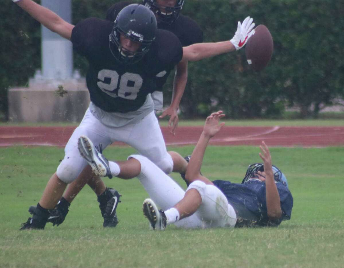 As a Yellowjacket defender hovers over a Texans receiver, a Sam Rayburn pass play falls incomplete in Friday night's scrimmage with Galena Park.