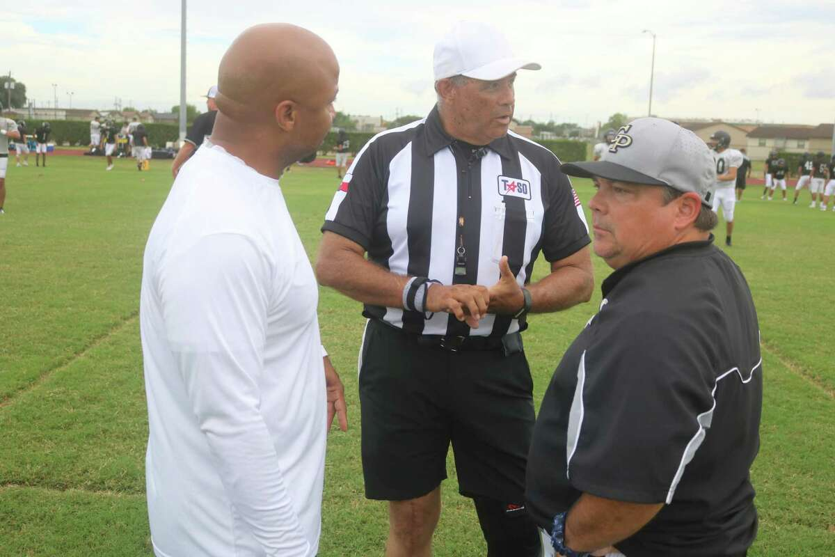 New Sam Rayburn head coach Desmond Stafford (left) and new Galena Park head coach Spiro Amarantos confer with referee Mike Massey over some ground rules for their Friday night scrimmage.