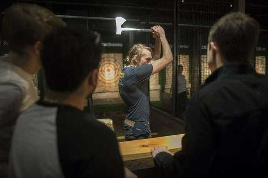 """In this March 3, 2018, photo, an """"axepert,"""" center, gives contestants instruction on hatchet throwing techniques and the rules of the game at the Kick Axe Throwing venue in the Brooklyn borough of New York. Kick Axe Throwing is the first bar in New York City to pick up on a nationwide trend of ax throwing. (AP Photo/Mary Altaffer)"""