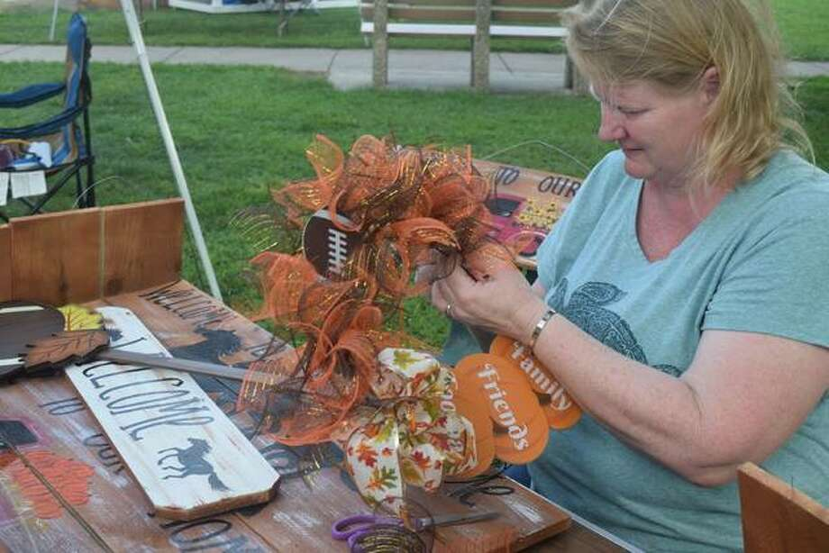 Cindy Gratton of Girard makes a wreath at the Waverly Picnic Friday. Photo: Samantha McDaniel-Ogletree | Journal-Courier