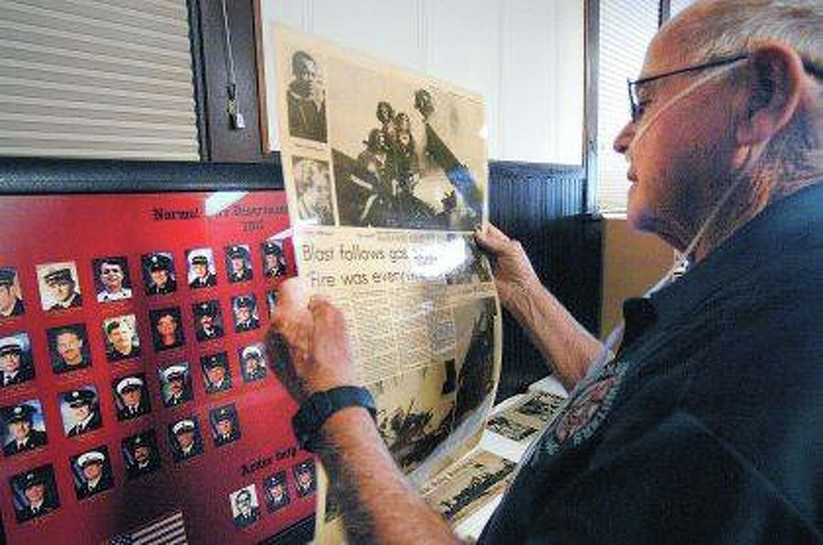Chuck Smalley, the first full-time inspector/firefighter for the Normal Fire Department, looks over newspapers that documented some of the worst fires in the town's history during a 50th anniversary party, at the Hudson Village Hall. The fire chronicled in the paper was a gas explosion that destroyed a house on Feb. 21, 1977. David Proeber   The Pantagraph (AP)