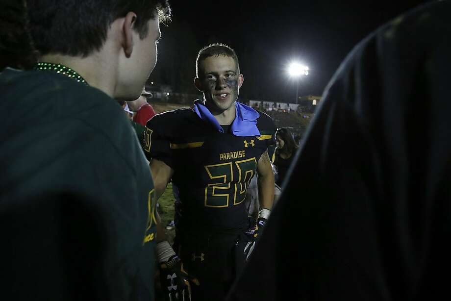 Paradise High School running back Lukas Hartley, center, talks with friends after defeating Williams High School 42-0 in Paradise, Calif., Friday, Aug. 23, 2019. This was the first game for the school since a wildfire last year that killed dozens and destroyed nearly 19,000 buildings including the homes of most of the players. (AP Photo/Rich Pedroncelli) Photo: Rich Pedroncelli / Associated Press