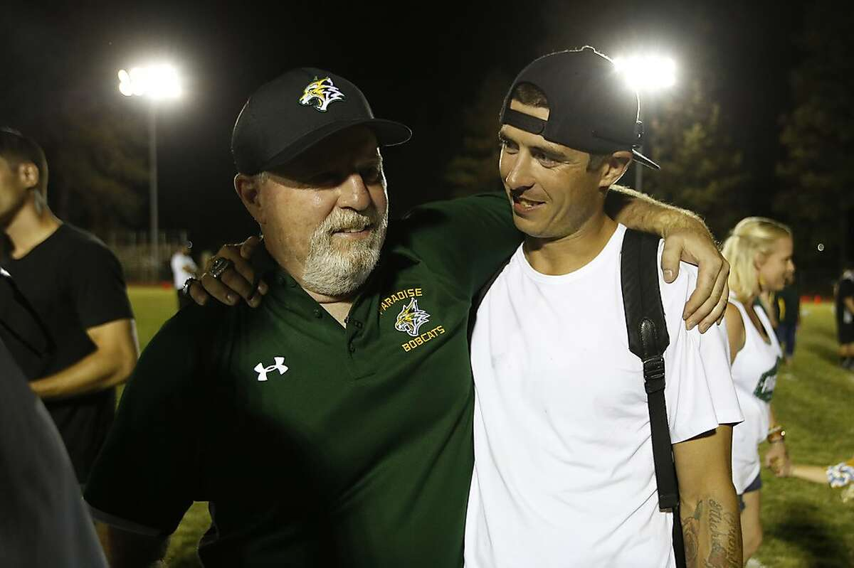 Paradise High School head coach Rick Prinz, left, is congratulated by former Paradise High School football player Jeff Maehl, who played five years in the NFL, for his 42-0 win over Williams High School Paradise, Calif., Friday, Aug. 23, 2019. This was the first game for the school since a wildfire last year that killed dozens and destroyed nearly 19,000 buildings including the homes of most of the players. (AP Photo/Rich Pedroncelli)