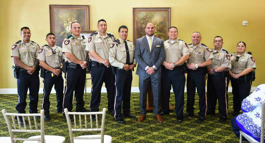 Webb County Judge Tano Tijerina, center right, is joined by Constable for Pct. 1 Rudy Gonzalez Jr., center left, and his deputies for a photo as Judge Tijerina is honored as this year's Angel of Hope Friday at La Posada Hotel's Tesoro room. Photo: Danny Zaragoza / Laredo Morning Times / Laredo Morning Times