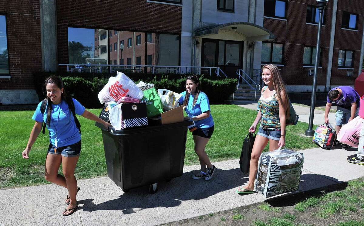 SCSU seniors Alyne Rodrigues, left, and Sarah Anderson, help bring in luggage for freshman Madison Macke, right, of Berlin, to the Chase Hall Dormitory. The students were arriving most of the day Saturday for the fall semester at Southern Connecticut State University.