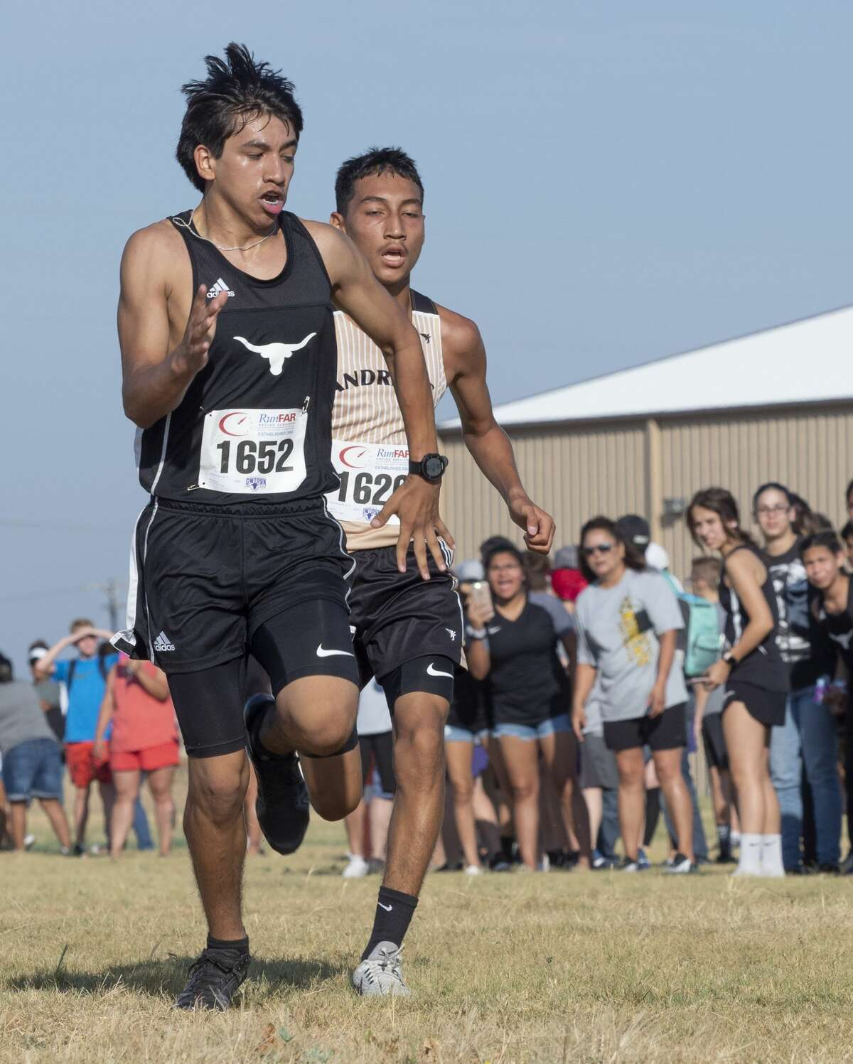 Big Spring's Roman Perez and Andrews' Derek Hernandez race to the finish line 08/24/19 morning in the boys Division 1 Tall City Cross Country Invitational at Rock the Desert grounds. Tim Fischer/Reporter-Telegram