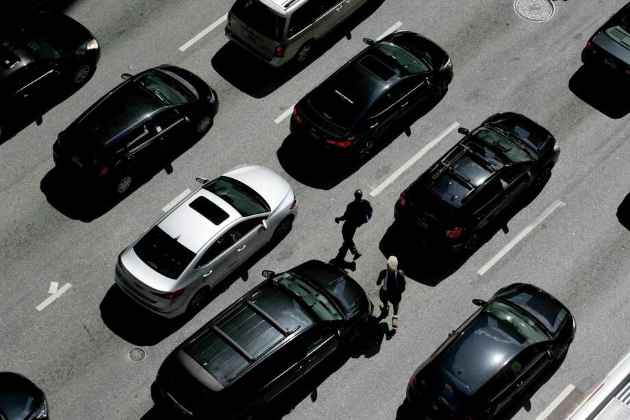 FILE - In this July 2, 2019, file photo men cross the street between vehicles waiting for a green light on East Lombard Street in downtown Baltimore. Ever since car-based SUVs passed sedans as the most popular vehicles in America a few years ago, automakers have been telling customers they get almost the same gas mileage as like-sized cars.  (AP Photo/Julio Cortez, File) Photo: Julio Cortez / Copyright 2019 The Associated Press. All rights reserved.