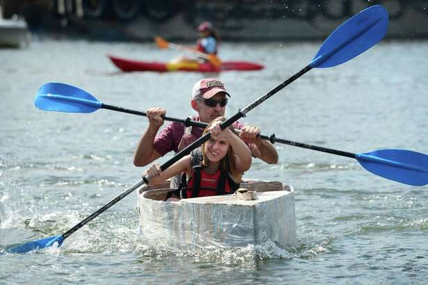 Chelsea Lovece and Tom Lovece paddle to win the Cardboard Kayak Race as SoundWaters hosts the fourth annual HarborFest on Saturday, August 24, 2019, at the Harbor Point Boardwalk in Stamford, Conn. The event featured a Dog costume parade and cardboard kayak race.