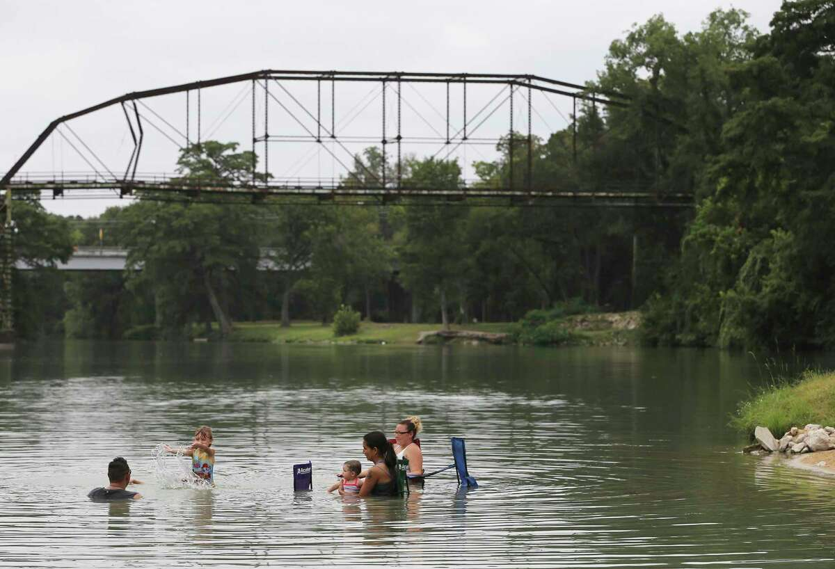 The Guelich family relaxes in the Guadalupe River, which feeds into Lake Placid. Residents have the option of forming a special tax district to keep the lake filled.