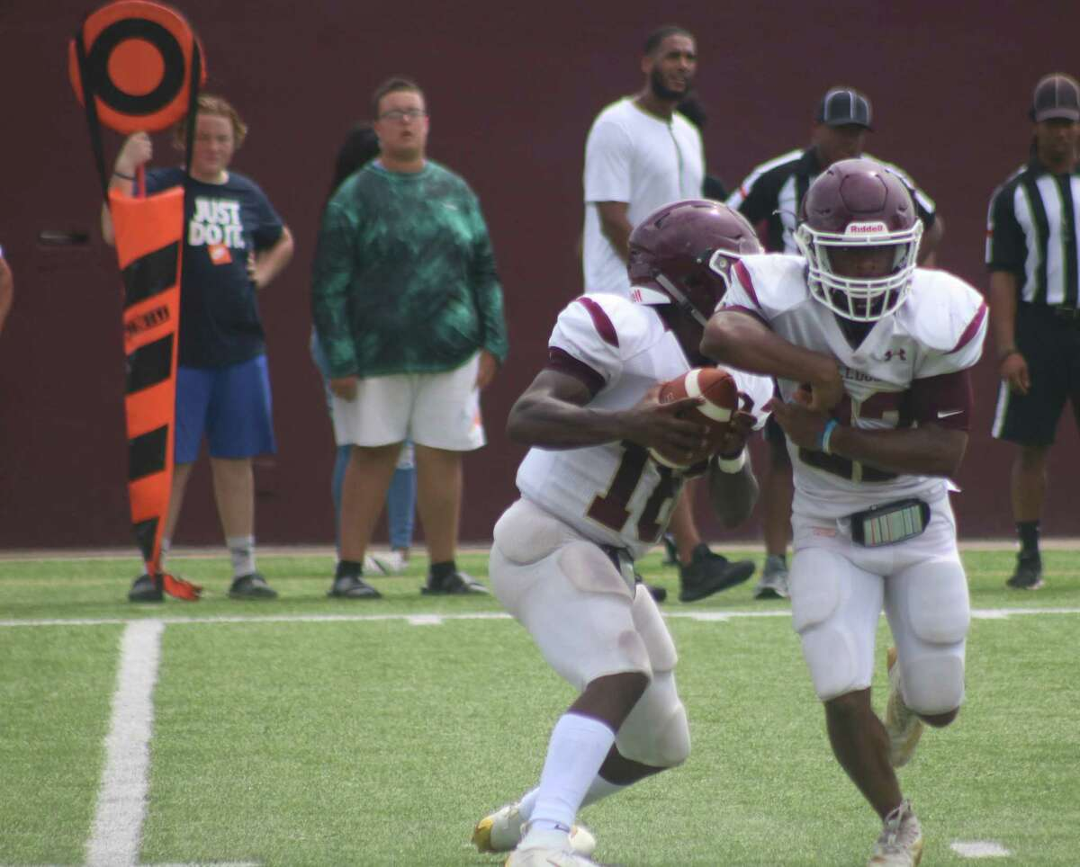 Summer Creek quarterback Bryan Bush (16) fakes the handoff to a running back and begins looking for yardage. Bush had a hand in 5 Bulldog touchdowns. The Deer can be thankful they faced 22-6A's MVP in a scrimmage and not a game that counts.