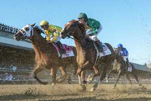 Code of Honor and jockey John Velazquez take some dirt from the field as they pass the finish line for the first time on the way to the win in the 150th running of the Travers Stakes at the Saratoga Race Course Saturday Aug. 24, 2019 in Saratoga Springs, N.Y. Photo special to the Times Union by Skip Dickstein