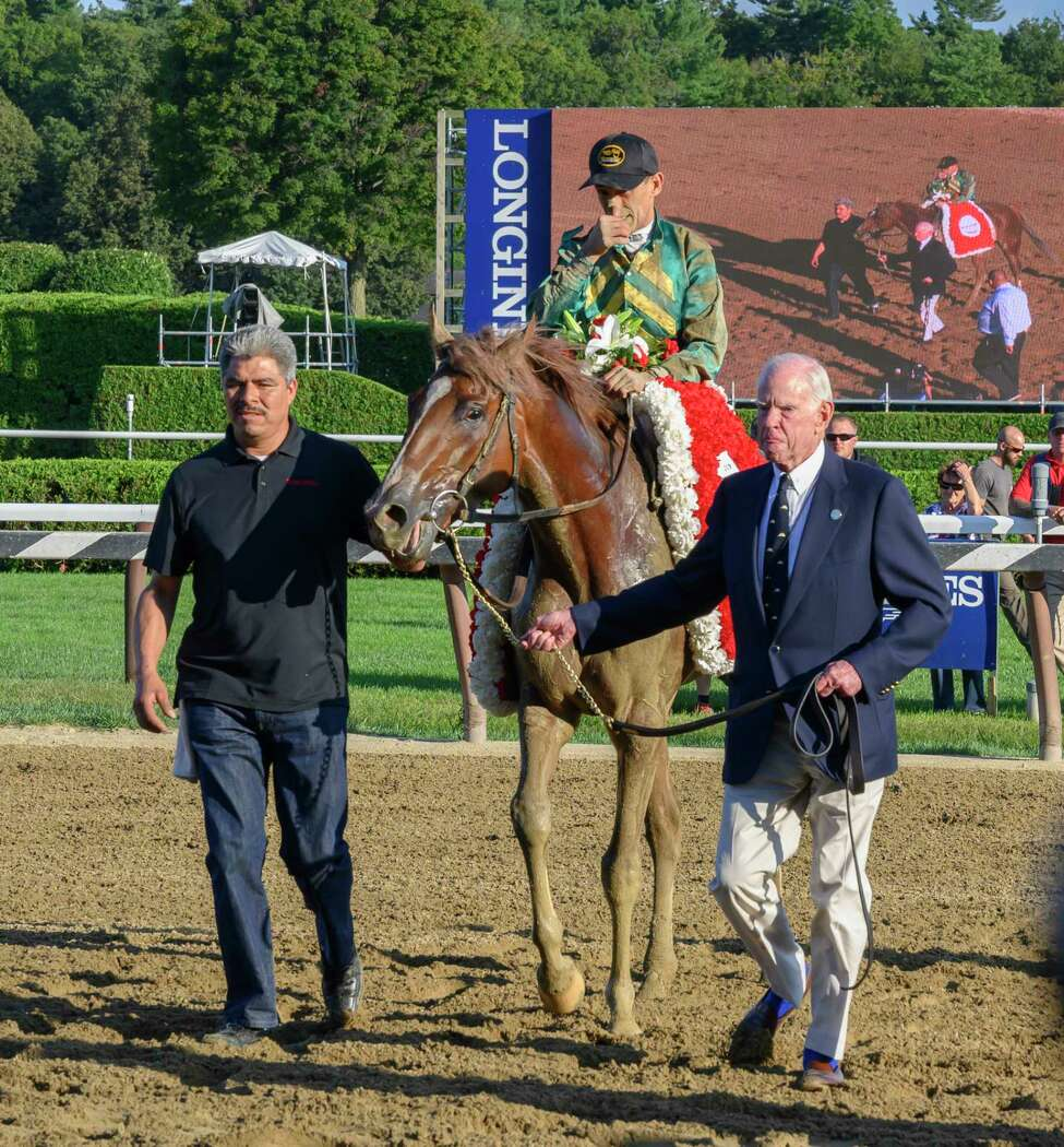 Owner Will Farish, right leads Code of Honor and jockey John Velazquez to the winner?•s circle after the win in the 150th running of the Travers Stakes at the Saratoga Race Course Saturday Aug. 24, 2019 in Saratoga Springs, N.Y. Photo special to the Times Union by Skip Dickstein