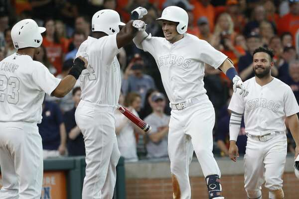 Houston Astros Alex Bregman (2) celebrates with Yordan Alvarez (44), and Michael Brantley (23) after hitting a three-run home run during the third inning of an MLB game at Minute Maid Park, Saturday, August 24, 2019.