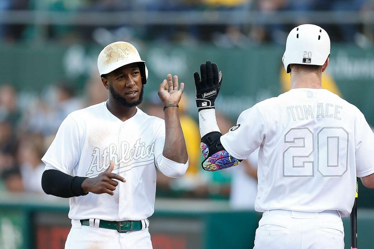 OAKLAND, CALIFORNIA - AUGUST 24: Jurickson Profar #23 of the Oakland Athletics celebrates with Mark Canha #20 after scoring on a double by Matt Chapman #26 in the bottom of the third inning against the San Francisco Giants at Ring Central Coliseum on August 24, 2019 in Oakland, California. Teams are wearing special color schemed uniforms with players choosing nicknames to display for Players' Weekend. (Photo by Lachlan Cunningham/Getty Images)