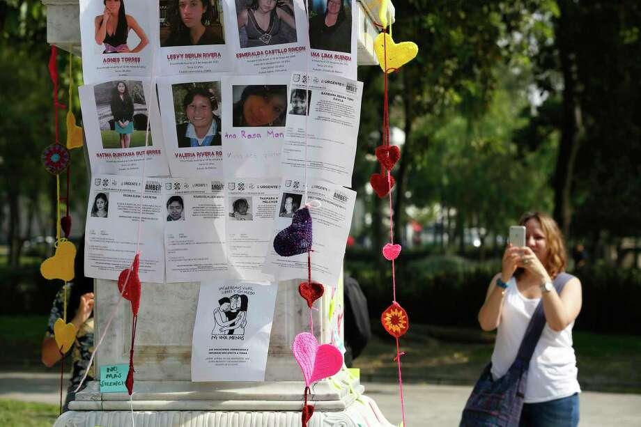 Una mujer toma una fotografía de un pilar cubierto con imágenes de víctimas durante un tributo a mujeres asesinadas, en la Alameda de la Ciudad de México, el sábado 24 de agosto de 2019. Un grupo de mujeres erigieron un altar hecho de corazones tejidos. Photo: Ginnette Riquelme /Associated Press / Copyright 2019 The Associated Press. All rights reserved.