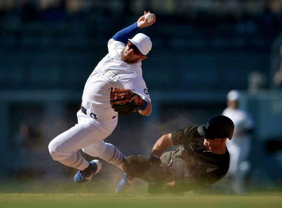 Los Angeles Dodgers second baseman Max Muncy falls while looking to throw to first after New York Yankees' Brett Gardner ran into him, on a grounder hit by Gio Urshela during the ninth inning of a baseball game in Los Angeles, Saturday, Aug. 24, 2019. The Dodgers won 2-1. (AP Photo/Kelvin Kuo) Photo: Kelvin Kuo / Copyright 2019 The Associated Press. All rights reserved.