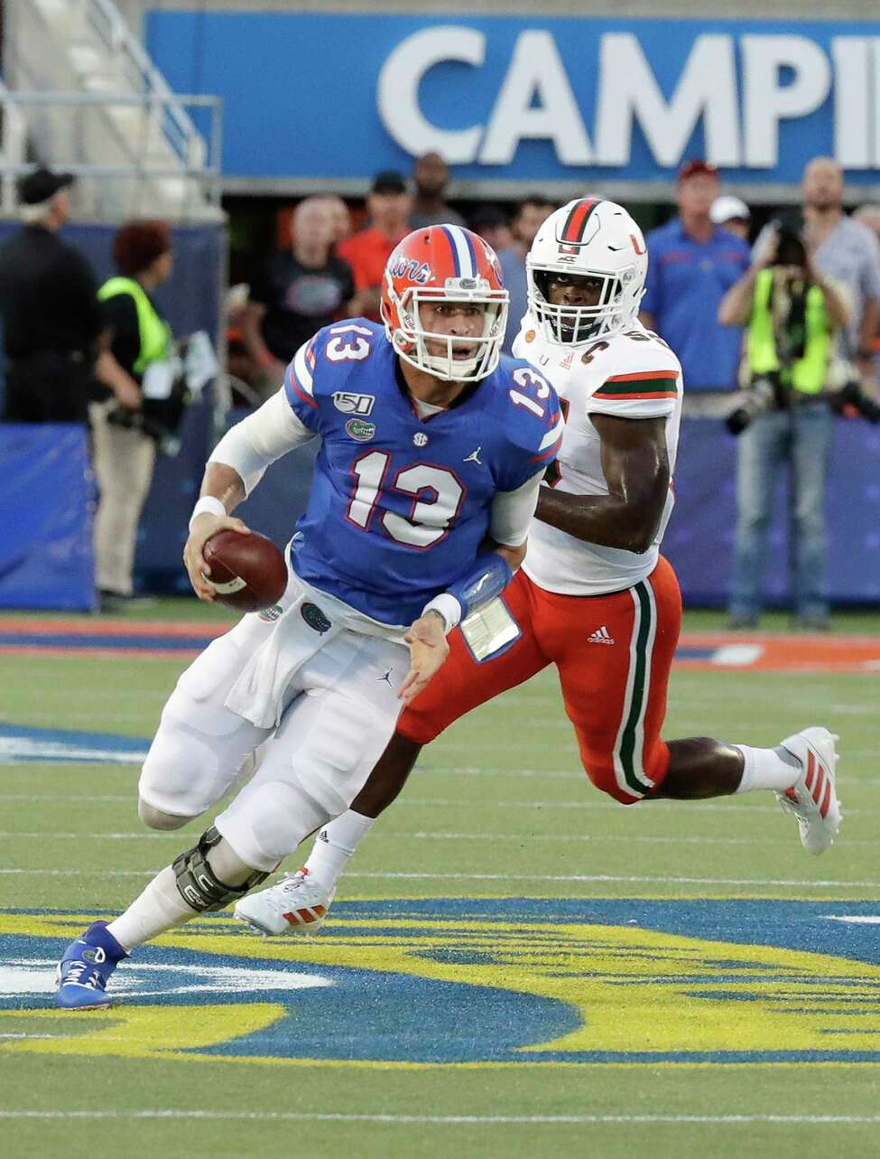 Florida quarterback Feleipe Franks (13) scrambles as he is pressured by Miami linebacker Shaquille Quarterman, right, during the first half of an NCAA college football game Saturday, Aug. 24, 2019, in Orlando, Fla. (AP Photo/John Raoux)