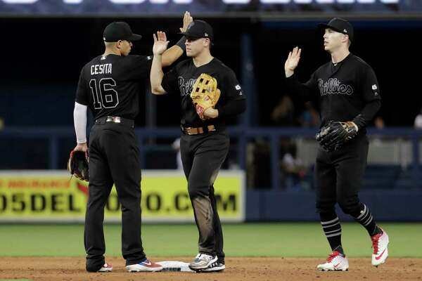 Philadelphia Phillies second baseman Cesar Hernandez (16), center fielder Scott Kingery, center, and left fielder Corey Dickerson, right, celebrate after a baseball game against the Miami Marlins, Saturday, Aug. 24, 2019, in Miami. (AP Photo/Lynne Sladky)