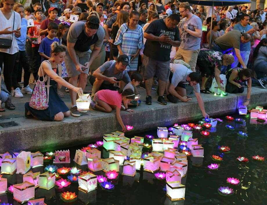 People place lanterns in the water during the Wishing Lanterns event on the River Walk on Saturday, Aug. 24, 2019. The event is a way for people to remember loved ones and to express their prayers, hopes and wishes. Photo: Billy Calzada, Staff Photographer / Billy Calzada
