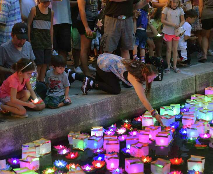 People place lanterns in the water during the Wishing Lanterns event on the River Walk on Saturday, Aug. 24, 2019. The event is a way for people to remember loved ones and to express their prayers, hopes and wishes.