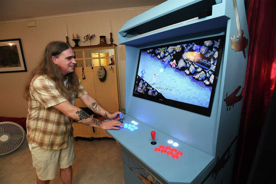 John Allen plays a Michael Jackson called Moonwalker on the arcade-style gaming machine that he recently built. Allen and his wife Amanda build the machine and sell them to fans. Photo taken Thursday, 8/15/19 Photo: Guiseppe Barranco/The Enterprise, Photo Editor / Guiseppe Barranco ©