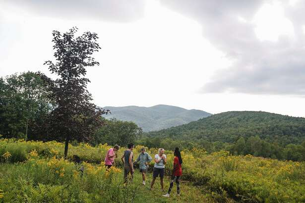 - PHOTO MOVED IN ADVANCE AND NOT FOR USE - ONLINE OR IN PRINT - BEFORE AUG. 25, 2019. - Women take in the view at the Huntington Open Women's Land in Huntington, Vt., Aug. 16, 2019. The area - once a residential community for lesbians, born out of the womyn's land movement of the 1960s and '70s - is now more of a rural retreat in danger of dying out. (Libby March/The New York Times)