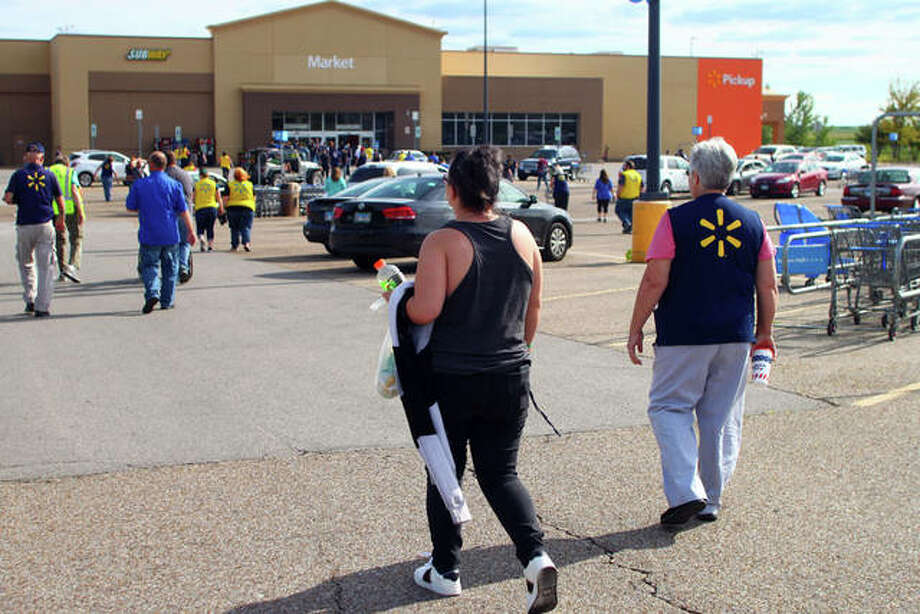 Customer Brittany Carroll walks closer to the Walmart entrance as employees go back into the store Saturday. The store was evacuated after a bomb threat was reported, according to police. Photo: Rosalind Essig | Journal-Courier