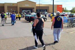 Customer Brittany Carroll walks closer to the Walmart entrance as employees go back into the store Saturday. The store was evacuated after a bomb threat was reported, according to police.