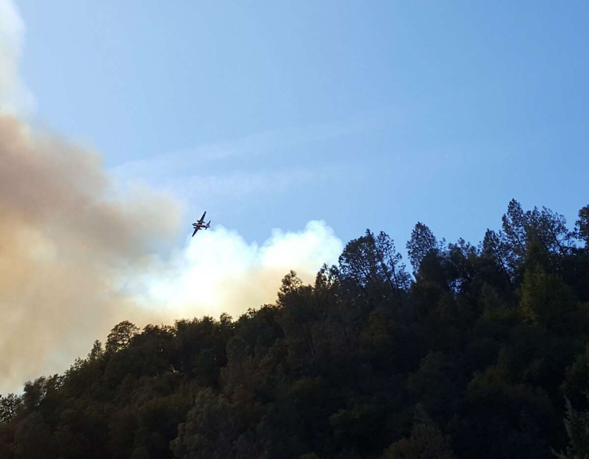 An aircraft battling the Mountain Fire is pictured flying above the smoke.
