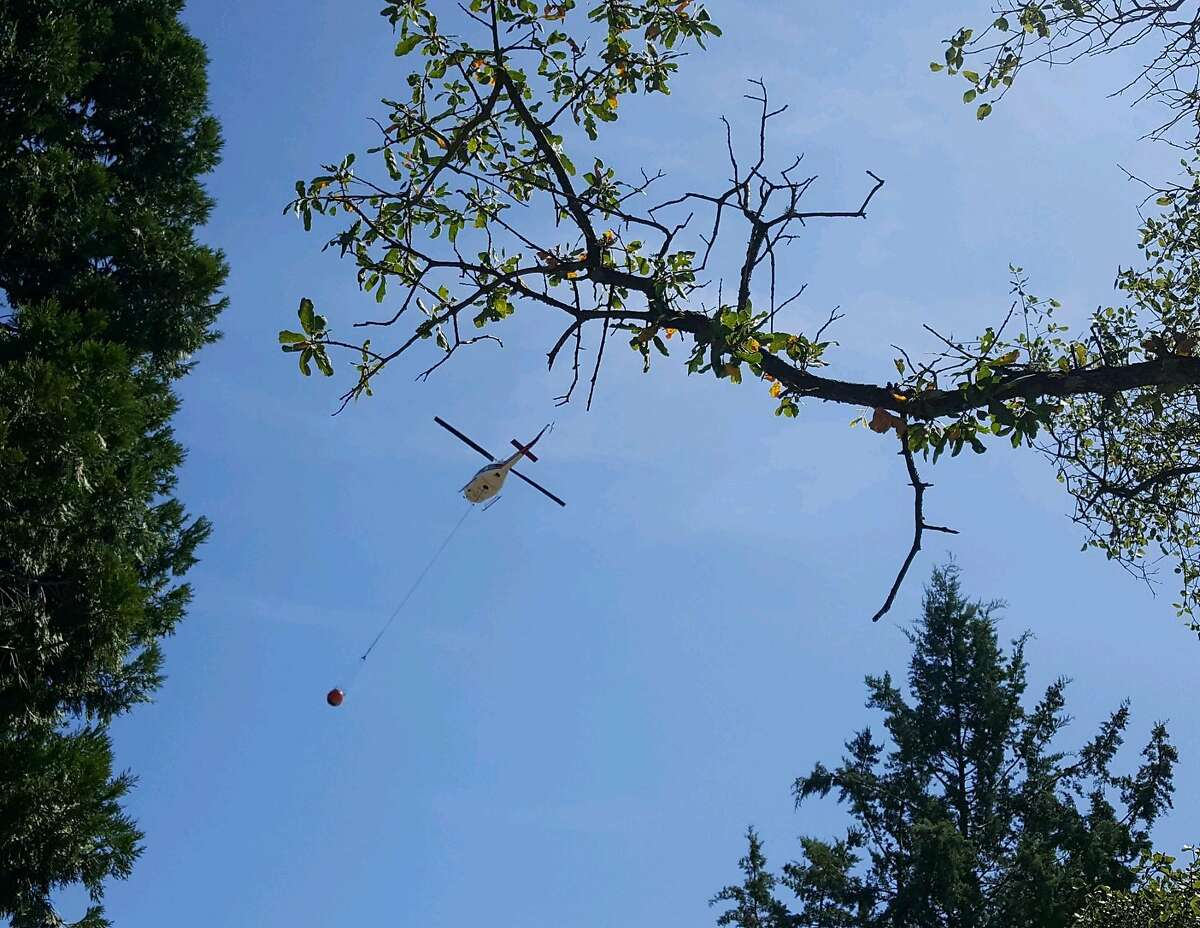 A helicopter departs from Palmer's property after picking up water from her pond.