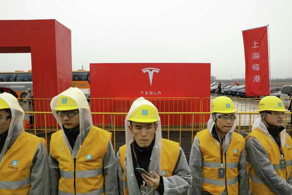 Workers in rain gear wait ahead of an event at a esla manufacturing facility in Shanghai in January 2019.