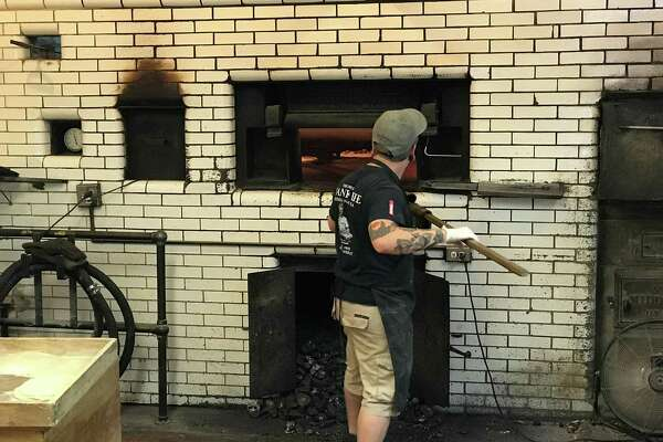 A pizza maker at the coal-fired oven at Frank Pepe Pizzeria Napoletana in New Haven, CT.