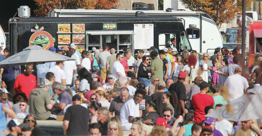 People line up for food at several trucks participating in the annual Alton Food Truck Expo, held Saturday at the Liberty Bank Alton Amphitheater. Almost two dozen trucks provided food ranging from doughnuts to upscale fries. The envent was sponsored by Sauce Magazine.