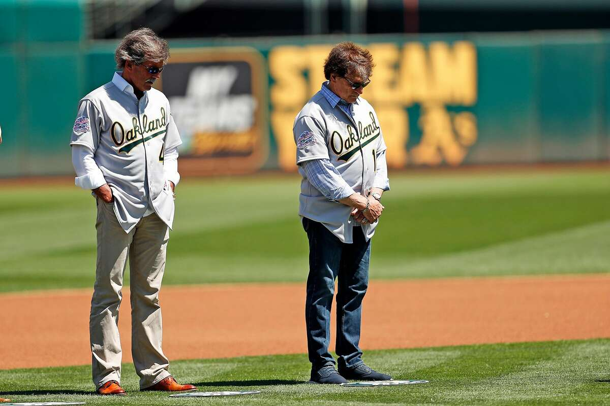 Oakland Athletics' Dennis Eckersleyand Tony LaRussa bow their heads during moment of silence for earthquake victims during ceremony honoring 1989 World Series champions before A's played San Francisco Giants in MLB game at Oakland Coliseum in Oakland, Calif., on Sunday, August 25, 2019.
