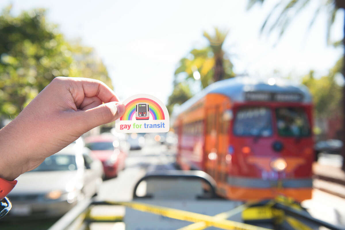 Chris Arvin holds one of his sticker designs up for a photo as a streetcar approaches.