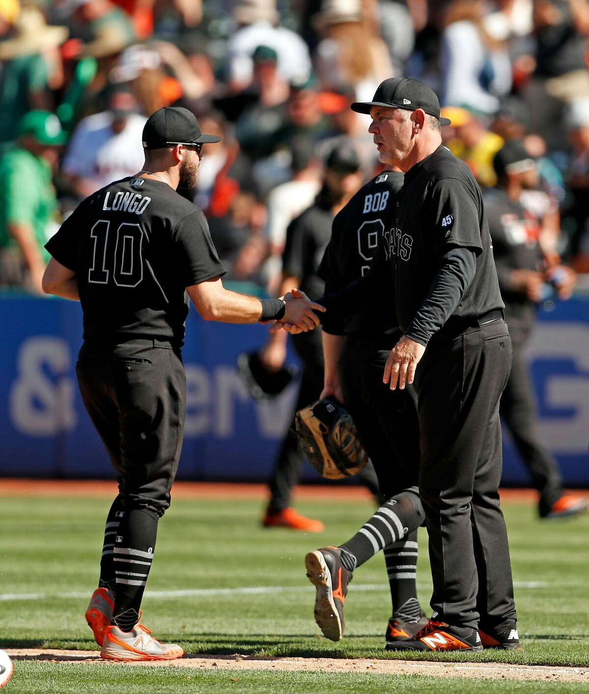 San Francisco Giants' manager Bruce Bochy shakes hands with Evan Longoria after 5-4 win over Oakland Athletics during MLB game at Oakland Coliseum in Oakland, Calif., on Sunday, August 25, 2019.