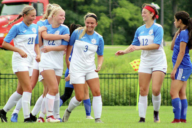 LCCC's Jocelyn Wagner (22) is congratulated after scoring a goal by teammates Emma Lucas (21), Payton Corley (3) and Cassie Hall (12) as Norma Garcia of Iowa Lakes looks on Sunday at LCCC.
