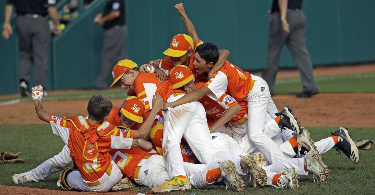 River Ridge, Louisiana's Stan Wiltz embraces Peyton Spadoni (6) on top of the pile as they celebrate the 8-0 win against Curacao in the Little League World Series Championship baseball game in South Williamsport, Pa., Sunday, Aug. 25, 2019. (AP Photo/Tom E. Puskar)