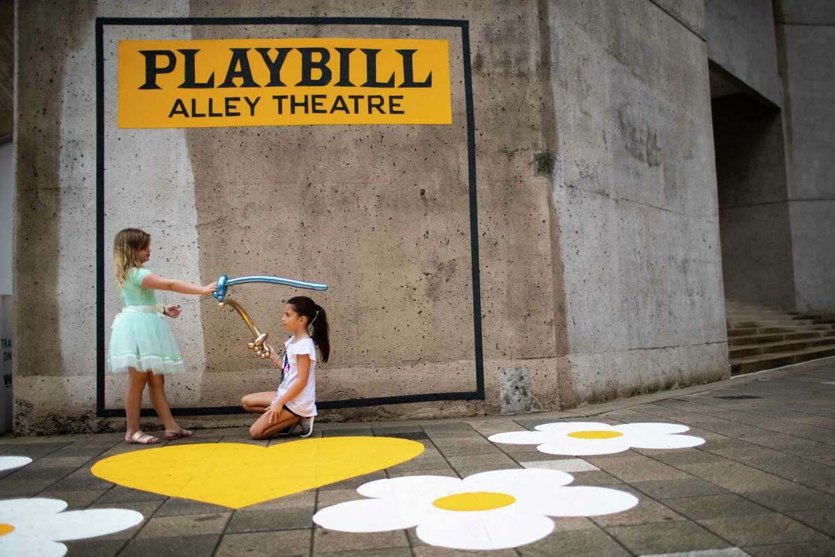 Millie Prouhet, 7, and Kenzie Younger, 7, pretend they are knights in front of a Playbill cover frame on an Alley Theatre wall during the Theater District Open House on Sunday, Aug. 25, 2019, in Houston. The girls stand on the Meet on the Heartsart installation created by Joan Dodd.