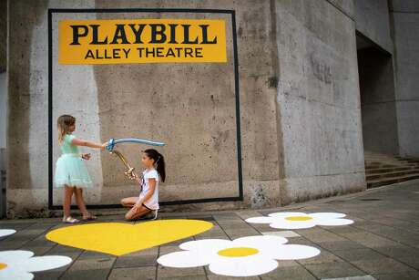 Millie Prouhet, 7, and Kenzie Younger, 7, pretend they are knights on front of a Playbill cover frame on a Alley Theatre wall during the Theater District Open House on Sunday, Aug. 25, 2019, in Houston.