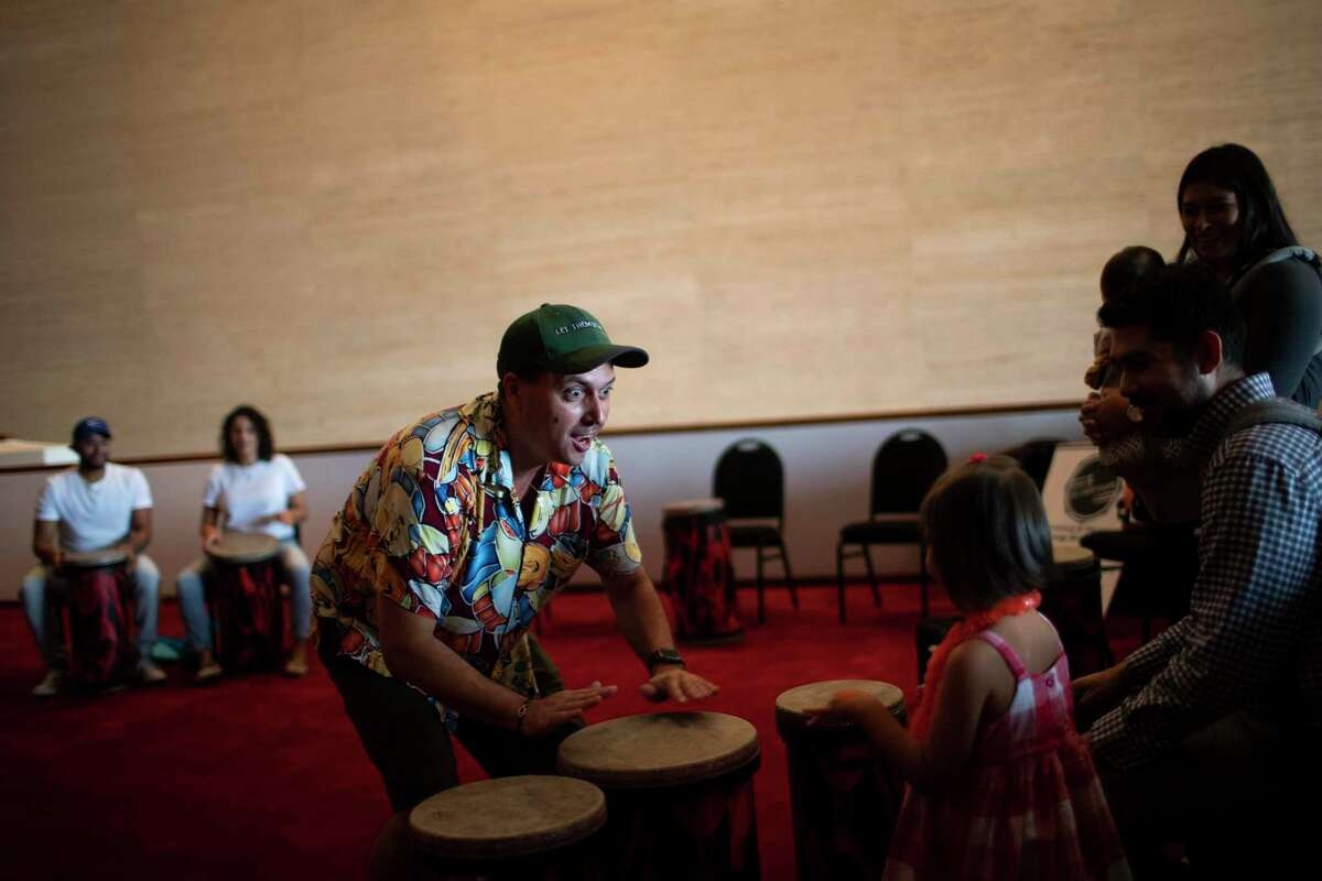 Ralph Hicks founder of Let Them Drum non-profit shows a little girl how to drum at the Jesse H. Jones Hall for the Performing Arts during the Theater District Open House on Sunday, Aug. 25, 2019, in Houston.