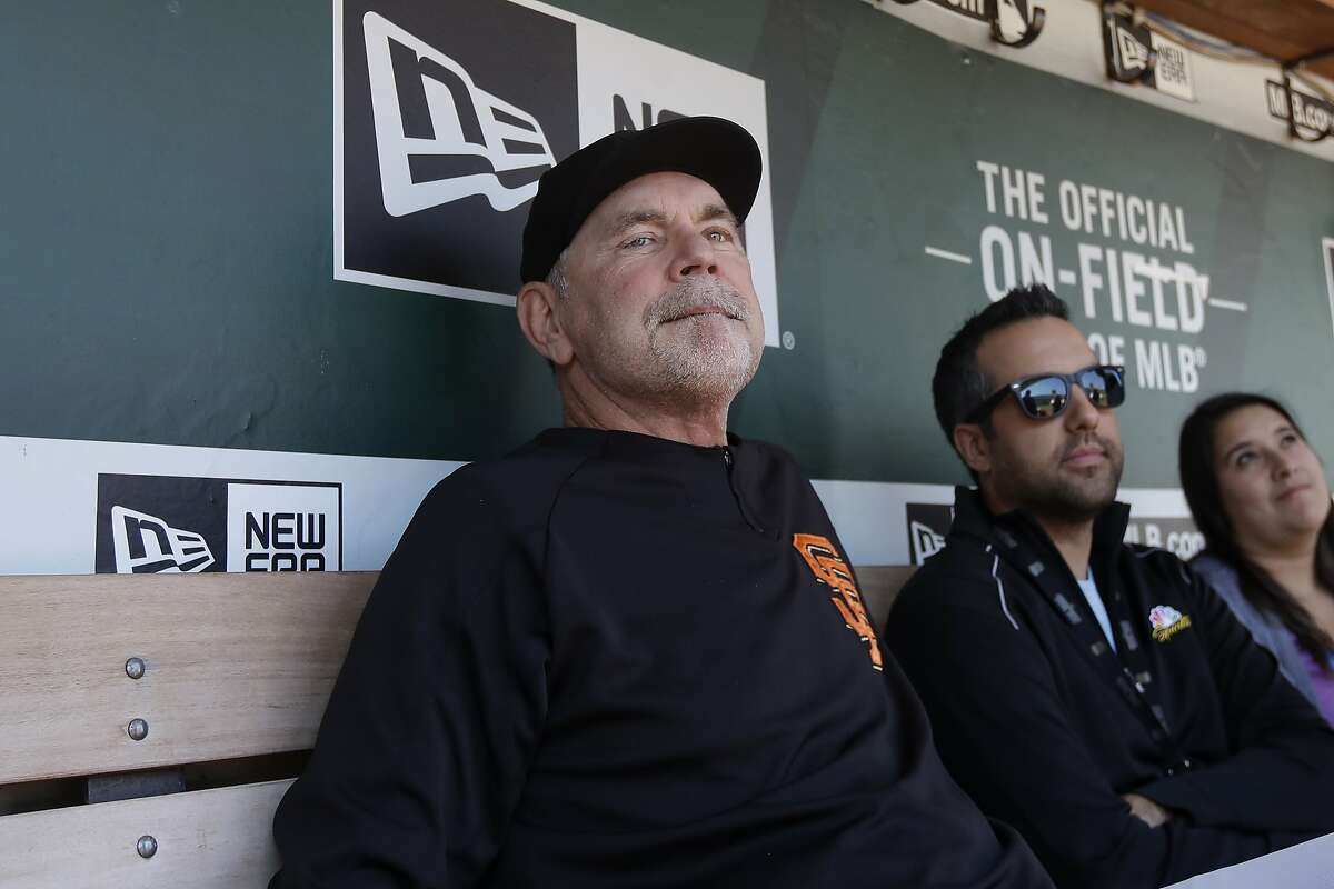 San Francisco Giants manager Bruce Bochy, left, talks to reporters before a baseball game against the Oakland Athletics in Oakland, Calif., Sunday, Aug. 25, 2019. (AP Photo/Jeff Chiu)