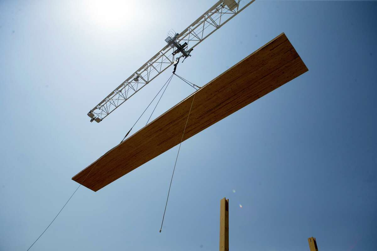 A floor piece is lifted above the Soto by a crane on Aug. 15, 2019. The building has more wood - 640 cubic meters - than usual for a six-story building and uses less steel and concrete. The wood was harvested from tree farms in Canada and Austria specially grown for mass timber construction. The wood is formed into massive beams and columns that are shipped to the building site and assembled there.
