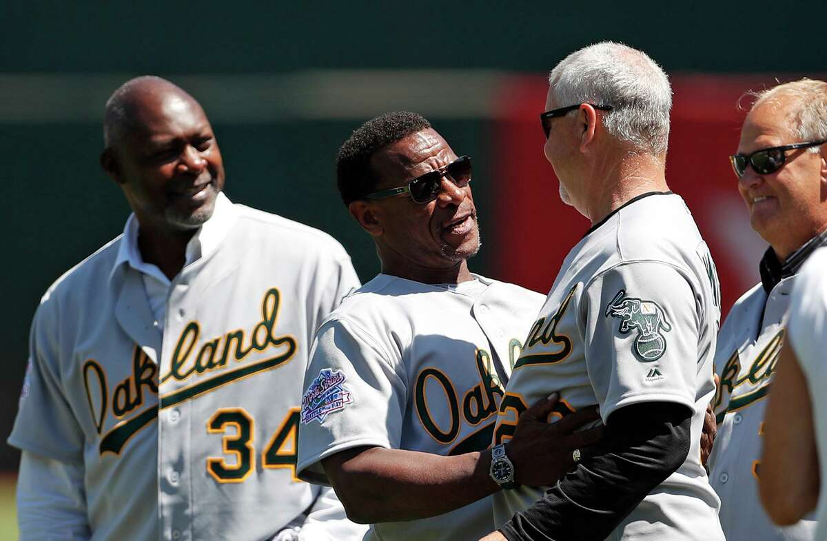Oakland Athletics' Rickey Henderson greets San Francisco Giants' pitching coach and former Athletic Curt Young during ceremony honoring 1989 World Series champions before MLB game at Oakland Coliseum in Oakland, Calif., on Sunday, August 25, 2019.